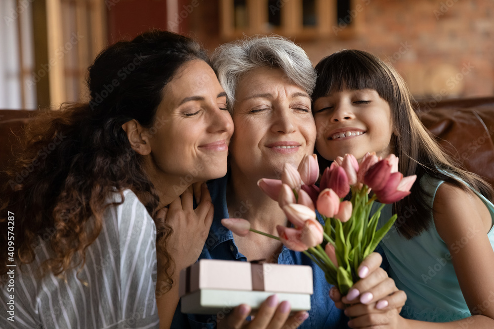 Fototapeta Close up happy three generations of women celebrating event, touching cheeks, cute little girl with young mother congratulating grandmother with birthday or 8 march, presenting gift and flowers