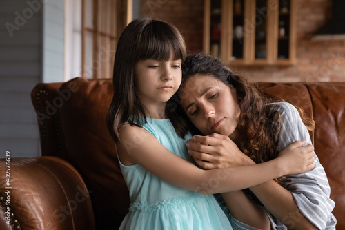 Tablou Canvas Close up caring little girl comforting, hugging depressed mother, sitting on cou