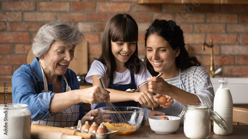 Happy little girl with smiling young mother and mature grandmother preparing dou Fototapet