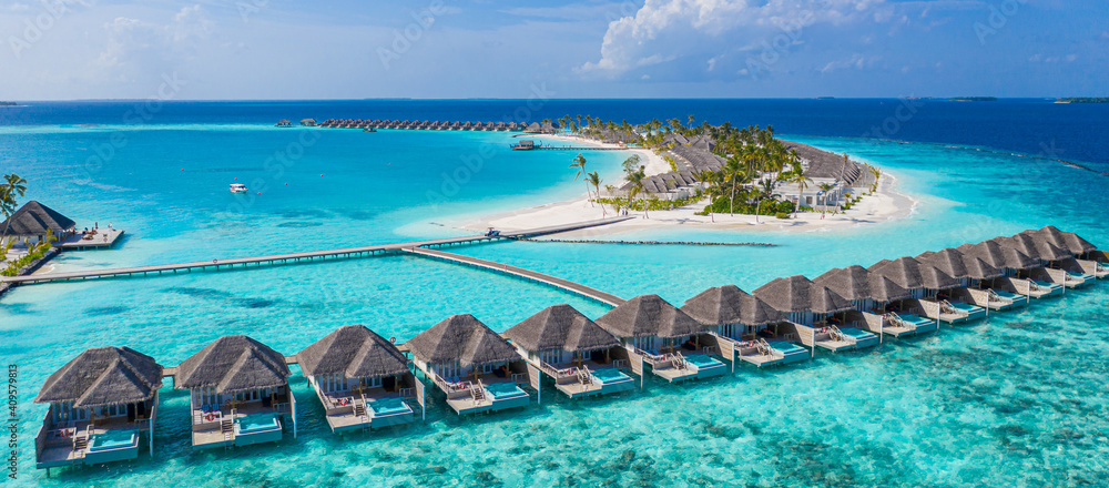 Fototapeta Aerial view of Maldives island, luxury water villas resort and wooden pier. Beautiful sky and ocean lagoon beach background. Summer vacation holiday and travel concept. Paradise aerial landscape pano