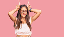 Young Hispanic Woman Wearing Casual Clothes And Glasses Doing Funny Gesture With Finger Over Head As Bull Horns