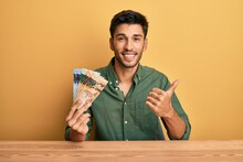 Young Handsome Man Holding Canadian Dollars Pointing To The Back Behind With Hand And Thumbs Up, Smiling Confident