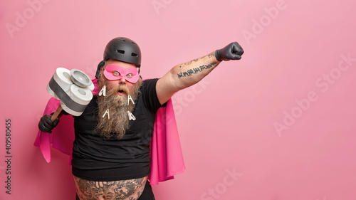 Obraz na plátně Surprised bearded man keeps mouth widely opened stretches tattooed arm holds tool for cleaning pretends to be superhero ready for actions isolated over pink background with copy space aside