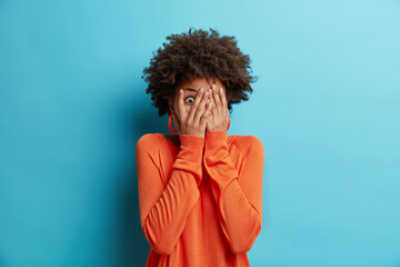 Scared African American woman covers face stares through fingers afraids of looking at something terrifying dressed in casual orange jumper isolated over blue background. People fright concept