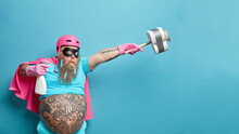 Surprised Bearded Man Wears Superhero Costume Stretches Arms Holds Detergent And Plunger Has Tattooed Belly Dressed In Undersized T Shirt Isolated Over Blue Background With Blank Copy Space.
