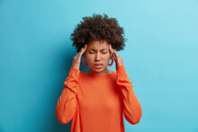Photo Of Frustrated Young Afro American Woman Has Headache Keeps Hands On Temples Suffers Unbearable Migraine After Noisy Party Wears Orange Sweater Poses Indoor Isolated On Blue Background.