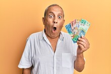 Handsome Mature Man Holding Australian Dollars Scared And Amazed With Open Mouth For Surprise, Disbelief Face