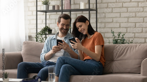 Fotografie, Obraz Overjoyed couple using phones together, sitting on cozy couch at home, happy man
