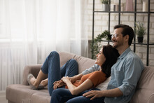 Happy Dreamy Young Couple Hugging, Relaxing On Cozy Couch Together, Renters Enjoying Leisure Time In New Apartment, Smiling Wife And Husband Planning Future, Sitting On Comfortable Sofa At Home
