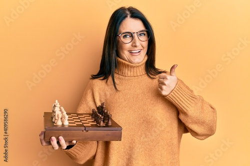 Obraz Middle age brunette woman holding chess board smiling happy and positive, thumb up doing excellent and approval sign - fototapety do salonu
