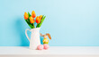 Orange tulip flowers bouquet in jug and pink easter eggs on shelf in front of blue wall. View with copy space