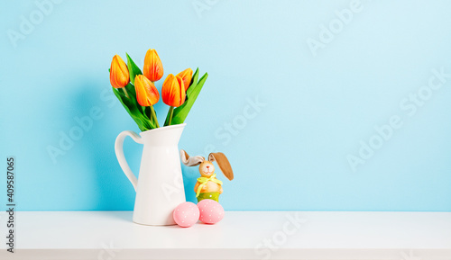 Fototapeta Orange tulip flowers bouquet in jug and pink easter eggs on shelf in front of blue wall. View with copy space obraz