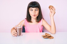 Young Little Girl With Bang Sitting On The Table Having Breakfast Making Fish Face With Mouth And Squinting Eyes, Crazy And Comical.