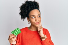 Young African American Girl Holding Birth Control Pills Serious Face Thinking About Question With Hand On Chin, Thoughtful About Confusing Idea