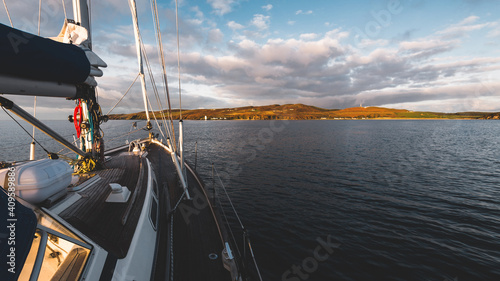 Sloop rigged modern yacht with wooden teak deck sailing near the shore of Isle of Islay at sunset. Inner Hebrides, Scotland, UK. Sport and recreation, travel destinations, landmarks, transportation