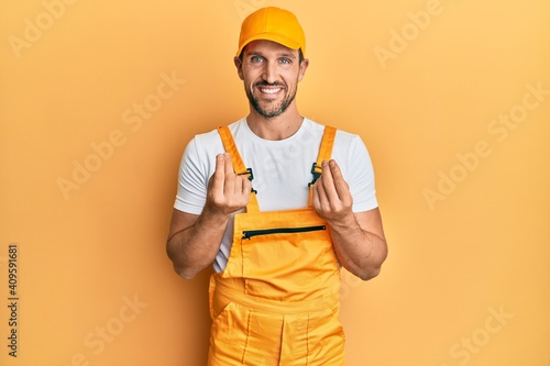 Obraz Young handsome man wearing handyman uniform over yellow background doing money gesture with hands, asking for salary payment, millionaire business - fototapety do salonu