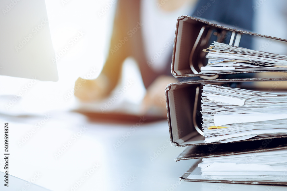 Fototapeta Binders with papers are waiting to be processed by business woman or bookkeeper working at the desk in office back in blur. Audit and tax concept
