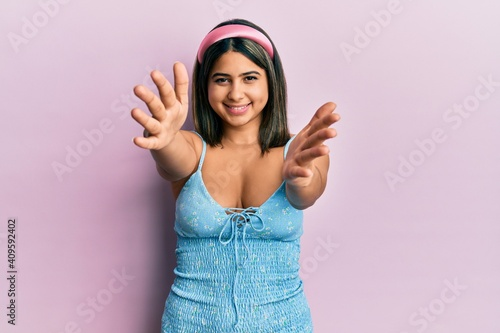Young latin woman wearing summer clothes looking at the camera smiling with open arms for hug Fototapeta