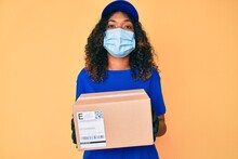 Young African American Woman Wearing Medical Mask Holding Delivery Package Angry And Mad Screaming Frustrated And Furious, Shouting With Anger Looking Up.