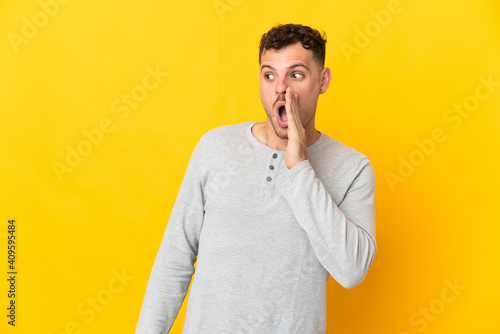 Obraz Young caucasian handsome man isolated on yellow background whispering something with surprise gesture while looking to the side - fototapety do salonu