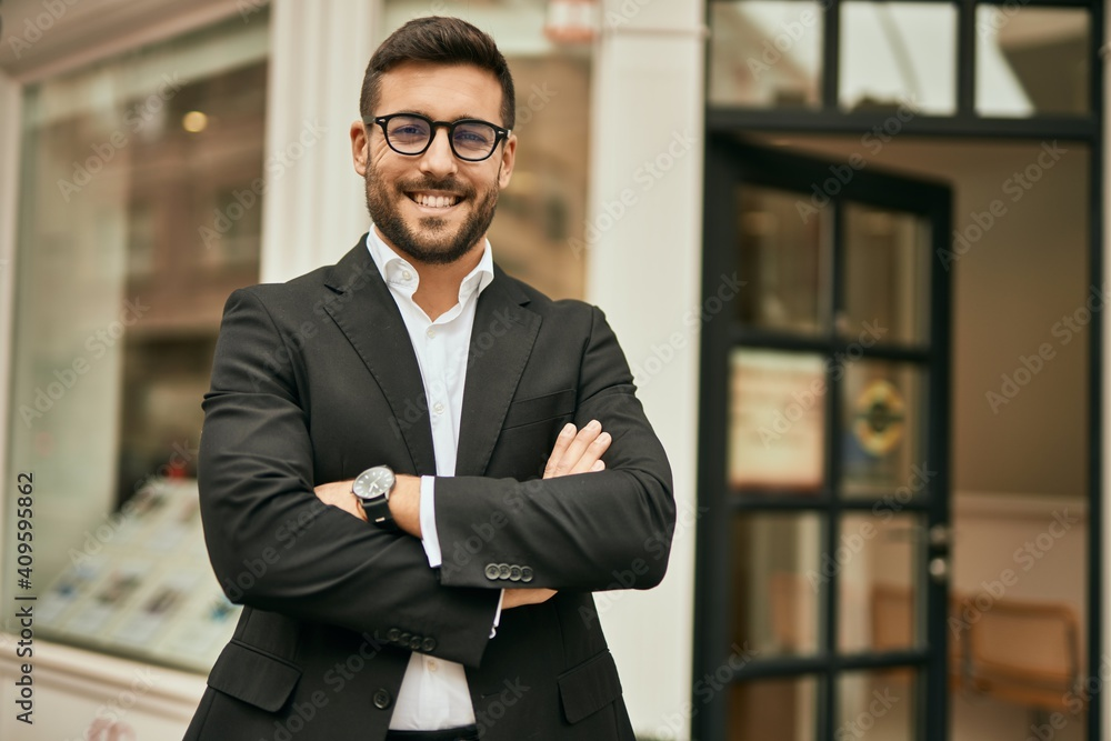 Fototapeta Young hispanic businessman with arms crossed smiling happy at the city.