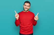 Young Hispanic Man Wearing Casual Clothes Smiling Confident Pointing With Fingers To Different Directions. Copy Space For Advertisement