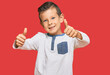 Leinwandbild Motiv Adorable caucasian kid wearing casual clothes approving doing positive gesture with hand, thumbs up smiling and happy for success. winner gesture.