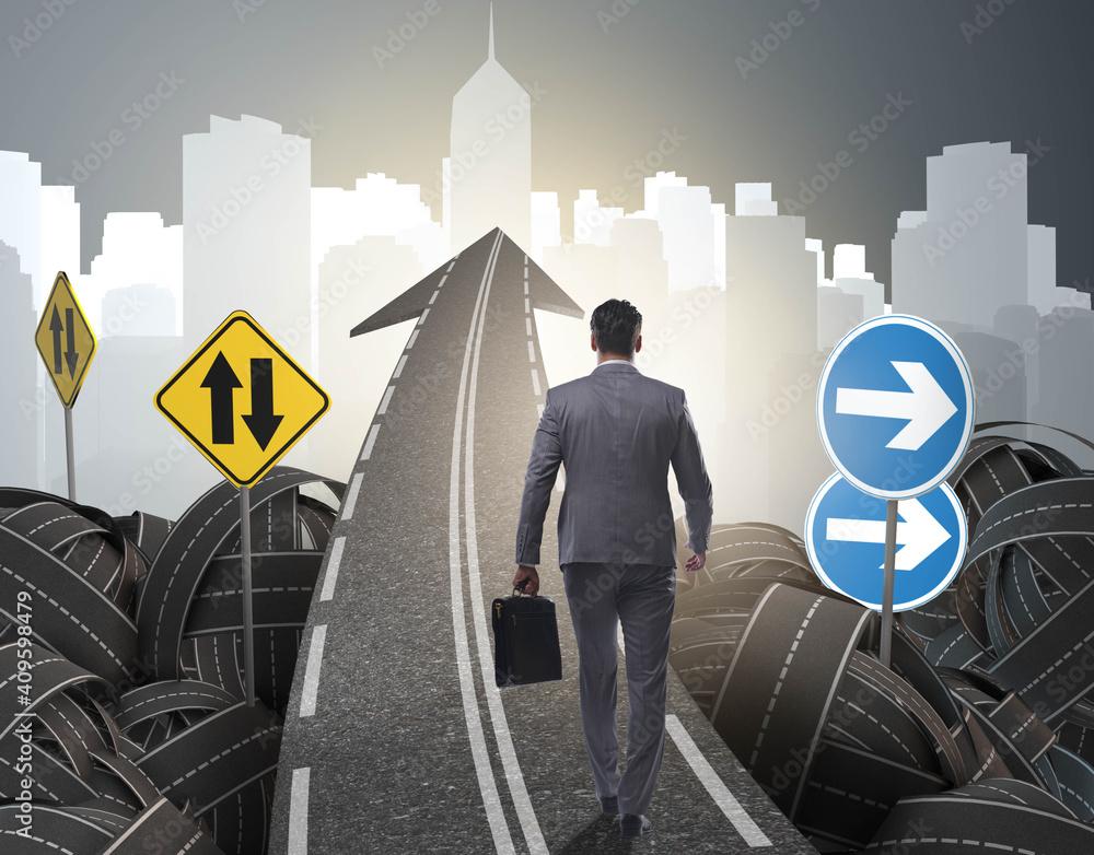 Fototapeta Businessman in uncertainty concept on road intersection crossroa