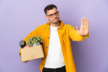Young Caucasian Man Making A Move While Picking Up A Box Full Of Things Isolated On Purple Background Making Stop Gesture And Disappointed