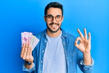 Young Hispanic Man Holding Indian Rupee Banknotes Doing Ok Sign With Fingers, Smiling Friendly Gesturing Excellent Symbol