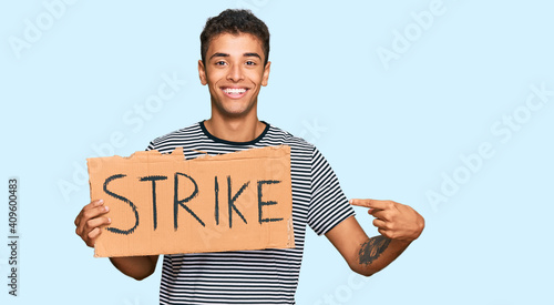 Obraz na plátně Young handsome african american man holding strike banner cardboard smiling happ