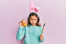 Little Beautiful Girl Wearing Cute Easter Bunny Ears Holding Colored Egg Skeptic And Nervous, Frowning Upset Because Of Problem. Negative Person.