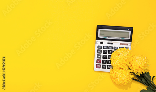 Fototapeta Big silver calculator, flower bouquet on yellow background with copy space, text place. Concept of business holiday or greeting card on woman day at the workplace. Professional accountant day. Mockup obraz