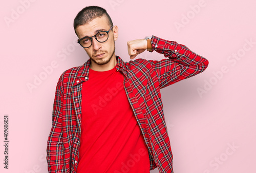 Obraz Hispanic young man wearing casual clothes strong person showing arm muscle, confident and proud of power - fototapety do salonu