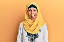 Middle Age Hispanic Woman Wearing Traditional Islamic Hijab Scarf Sticking Tongue Out Happy With Funny Expression. Emotion Concept.