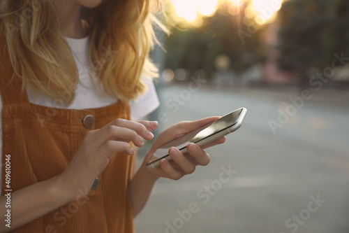 Fototapeta Woman ordering taxi with smartphone on city street, closeup