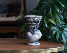 Abstract Syle Ceramic Vase - Bird Shape With Stylized Animals - On A Wooden Table, In The Background Plants