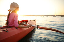 Little Girl Kayaking On River At Sunset. Summer Camp Activity
