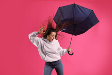 Emotional Woman With Umbrella Caught In Gust Of Wind On Pink Background