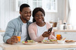 Happy African American Spouses Using Smartphone While Having Breakfast In Kitchen