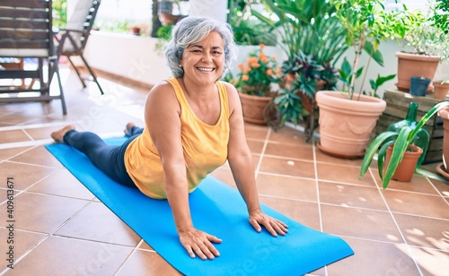 Fototapeta Middle age woman with grey hair smiling happy doing exercise and stretching on the terrace at home obraz