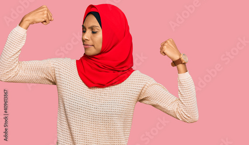 Cuadros en Lienzo Young african american woman wearing traditional islamic hijab scarf showing arms muscles smiling proud