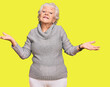 Leinwandbild Motiv Senior grey-haired woman wearing casual winter sweater smiling showing both hands open palms, presenting and advertising comparison and balance