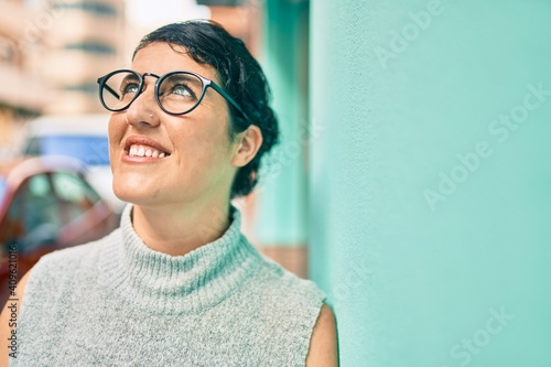 Obraz Young plus size woman smiling happy leaning on the wall at the city. - fototapety do salonu