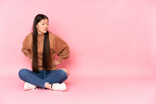 Young Asian Woman Sitting On The Floor Isolated On Pink Background Suffering From Backache For Having Made An Effort
