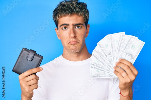 Obraz Young handsome man holding wallet and dollars banknotes depressed and worry for distress, crying angry and afraid. sad expression. - fototapety do salonu