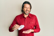 Middle Age Handsome Man Taking Pills Winking Looking At The Camera With Sexy Expression, Cheerful And Happy Face.