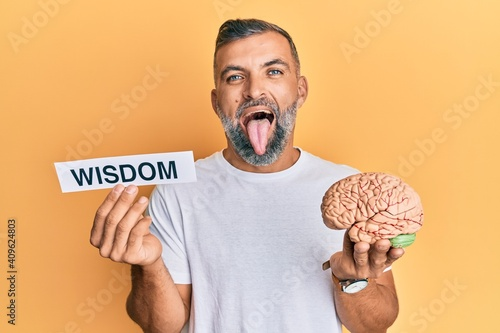 Middle age handsome man holding wisdom word on paper and brain sticking tongue out happy with funny expression.
