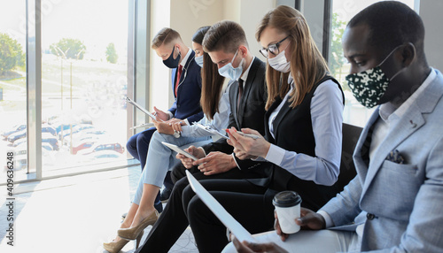 Obraz Stressful business people waiting for job interview with face mask, social distancing quarantine during COVID19 affect. - fototapety do salonu