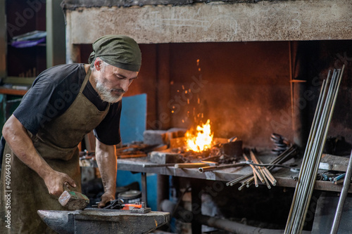 Old blacksmith working metal with hammer on the anvil in the forge Poster Mural XXL